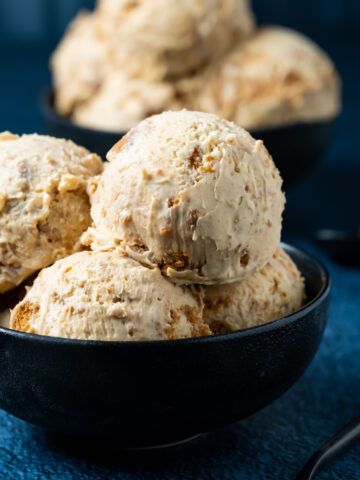 Scoops of biscoff ice cream in a black bowl.