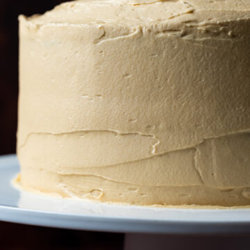 Frosted coffee cake on a white cake stand.