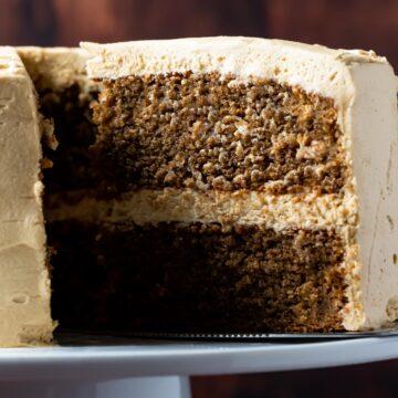 Sliced eggless coffee cake on a white cake stand.