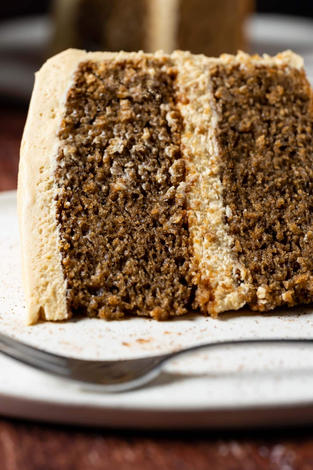 Slice of eggless coffee cake on a white plate with a cake fork.