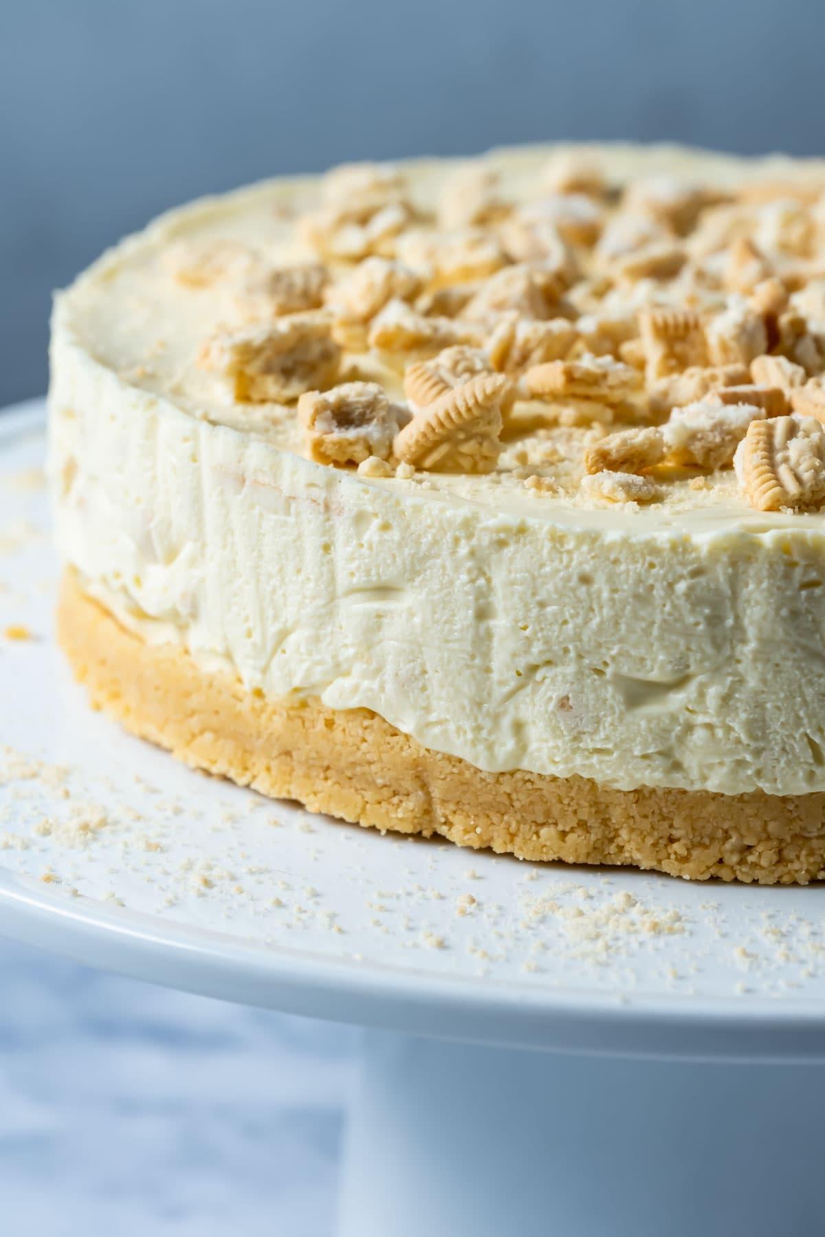 Golden oreo cheesecake on a white cake stand.