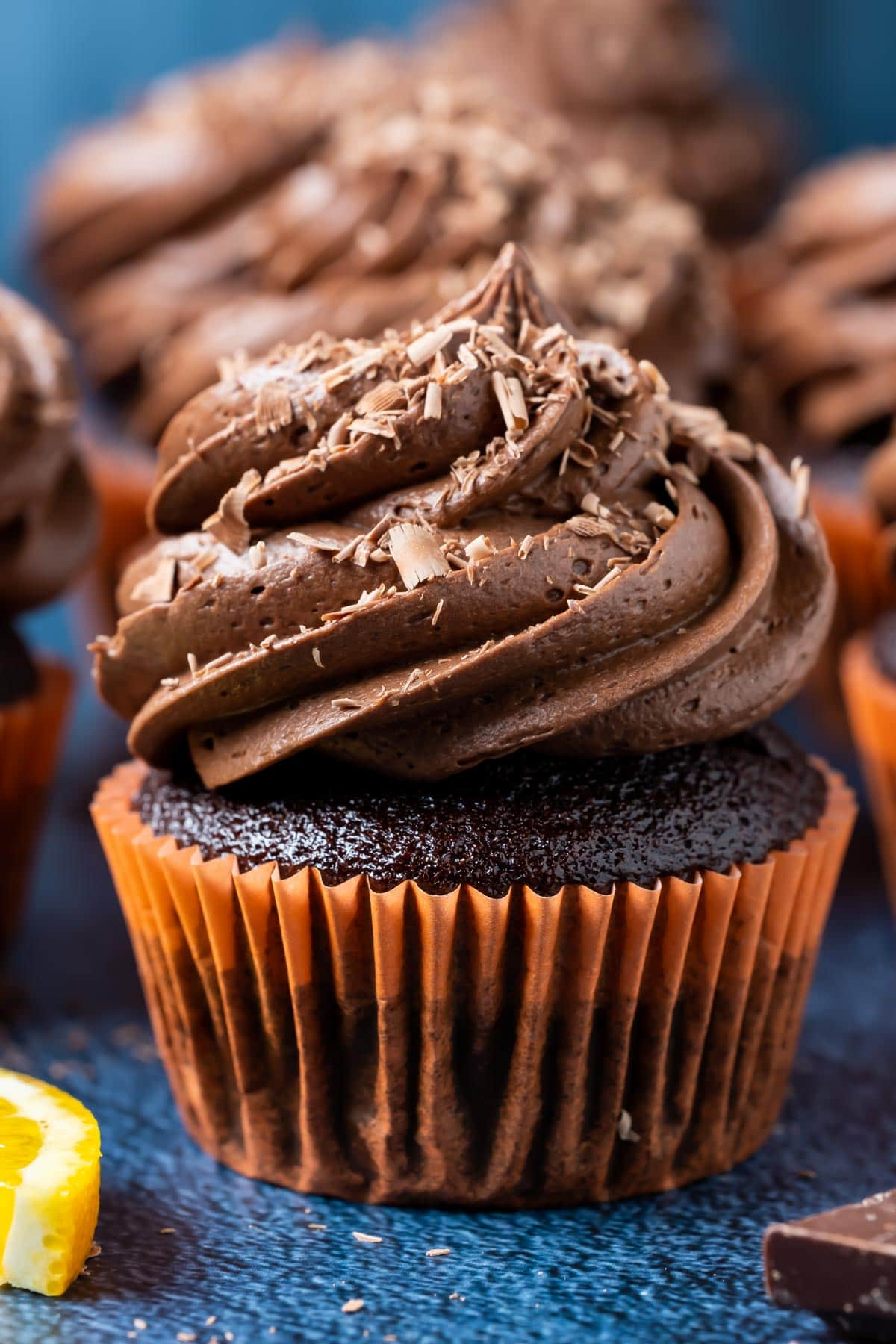Chocolate orange cupcakes topped with frosting and chocolate shavings.