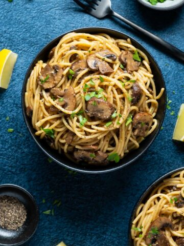 Mushroom pasta topped with fresh chopped parsley in a black bowl.