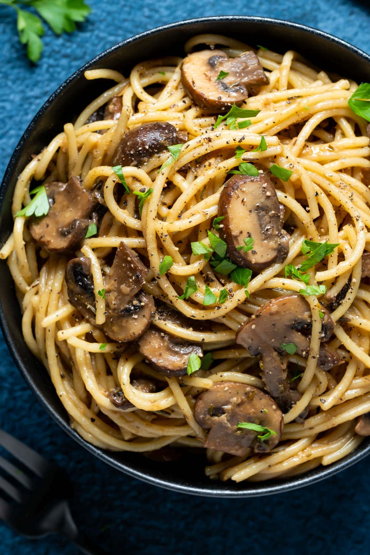 Pasta with mushrooms and fresh chopped parsley in a black bowl.