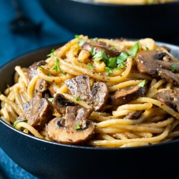 Mushroom pasta topped with fresh parsley in a black bowl.