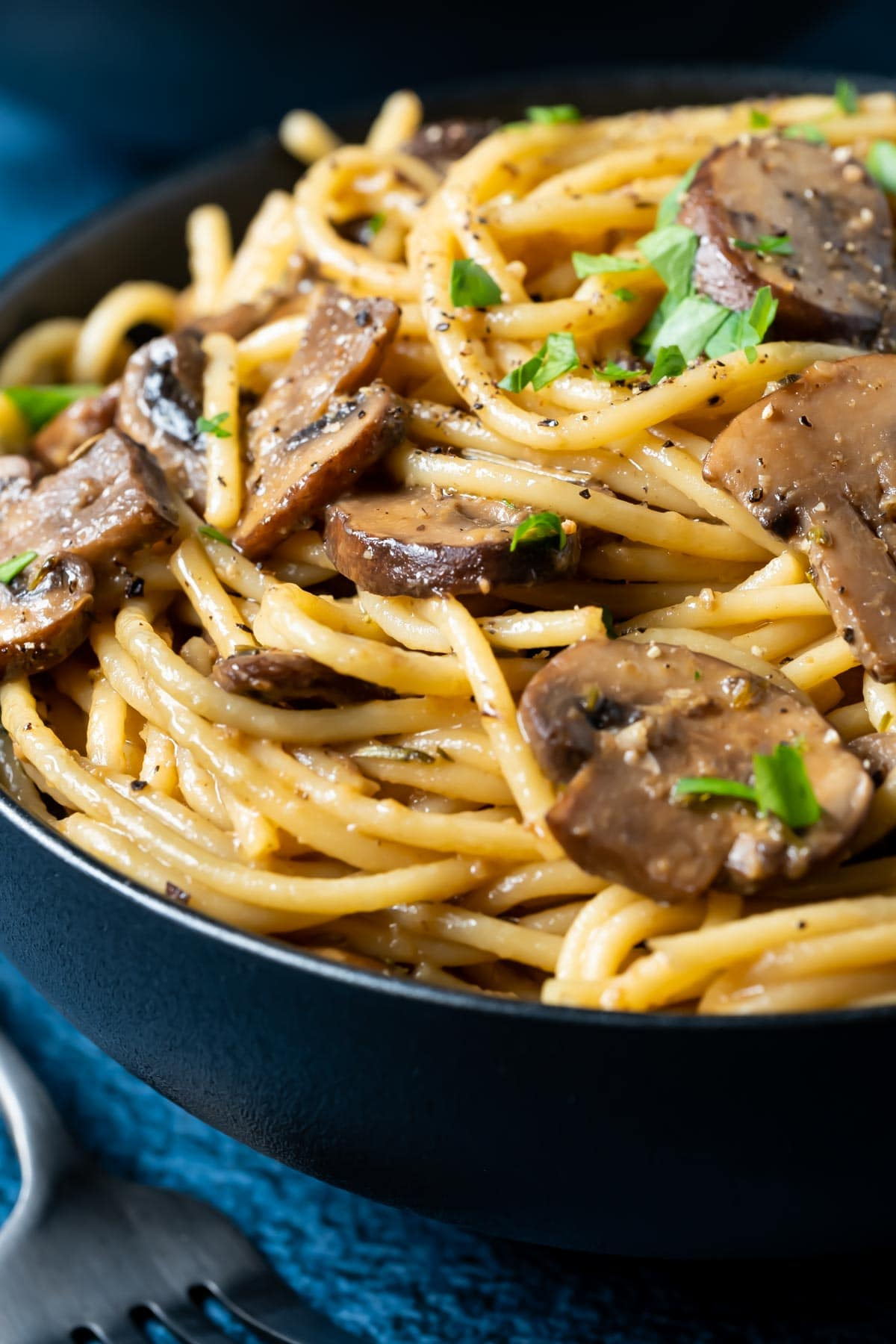 Pasta with mushrooms and fresh parsley in a black bowl.