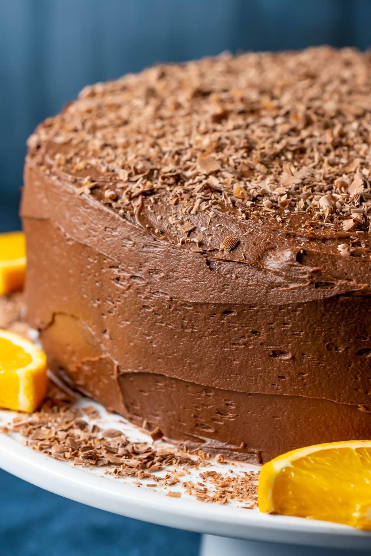 Chocolate orange cake on a white cake stand with orange slices.