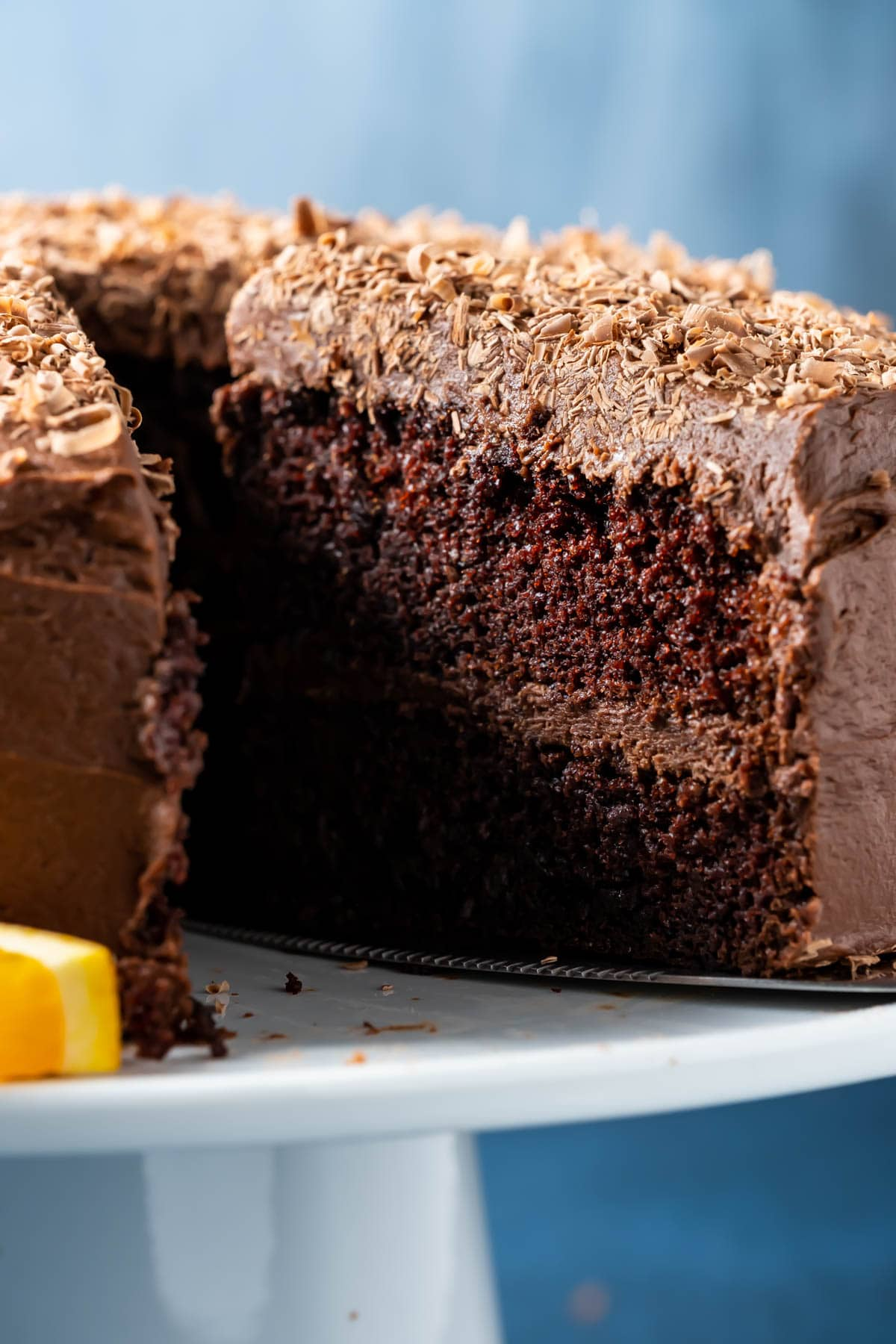 Sliced chocolate orange cake on a white cake stand.