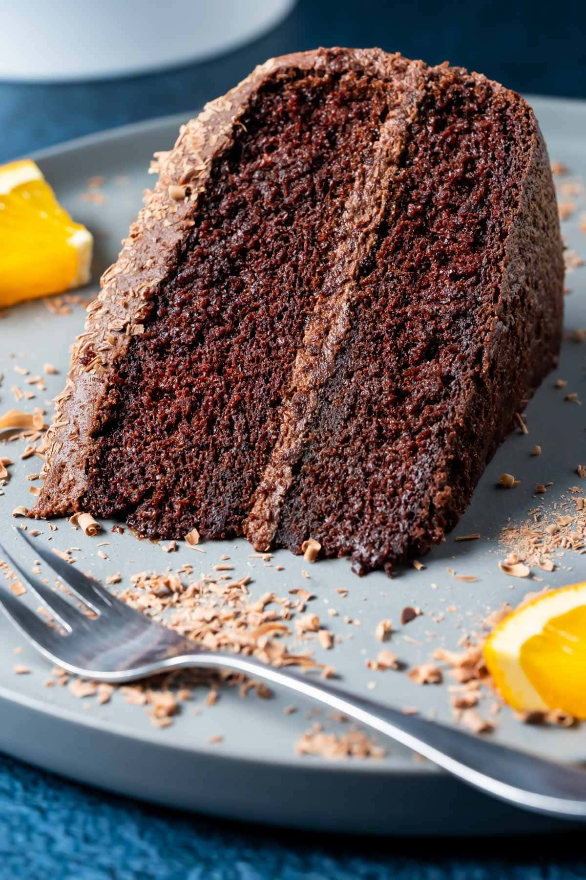 Slice of chocolate orange cake on a plate with a cake fork.