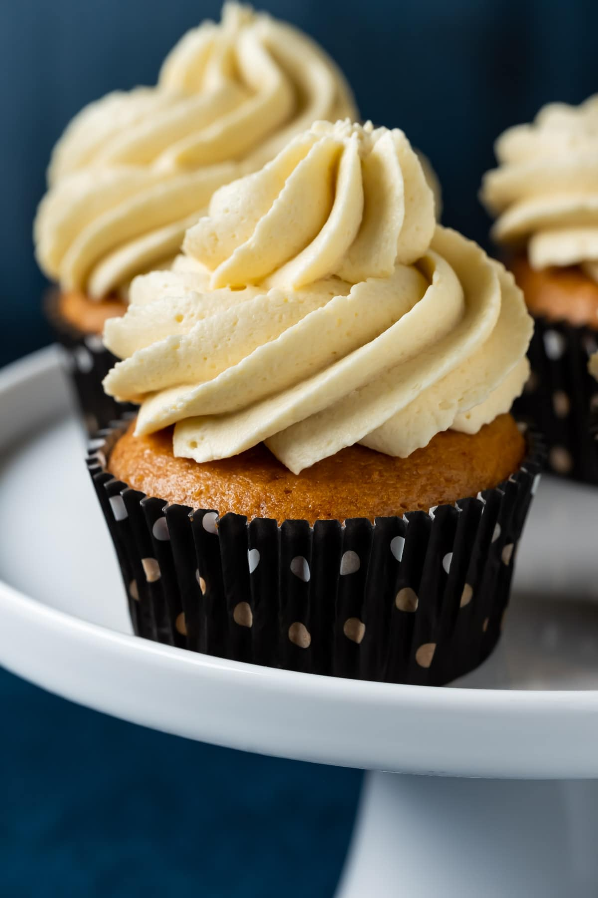 Eggless vanilla cupcakes on a white cake stand.